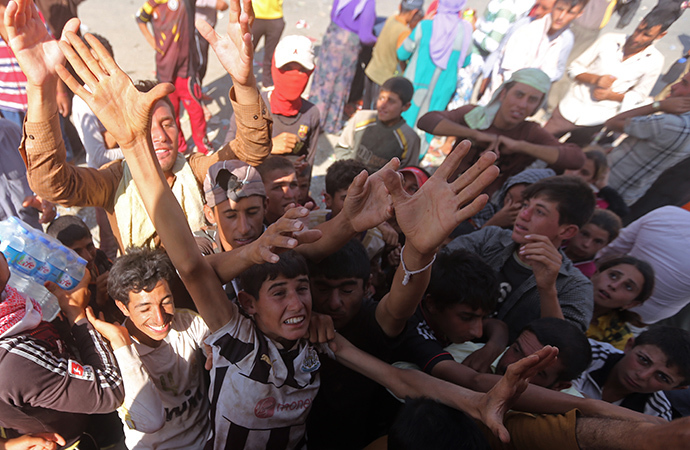 Displaced Iraqi Yazidis, who fled a jihadist onslaught on Sinjar, gather to collect bottles of water at the Bajid Kandala camp in Kurdistan's western Dohuk province, on August 13, 2014. (AFP Photo / Ahmad Al-Rubaye)