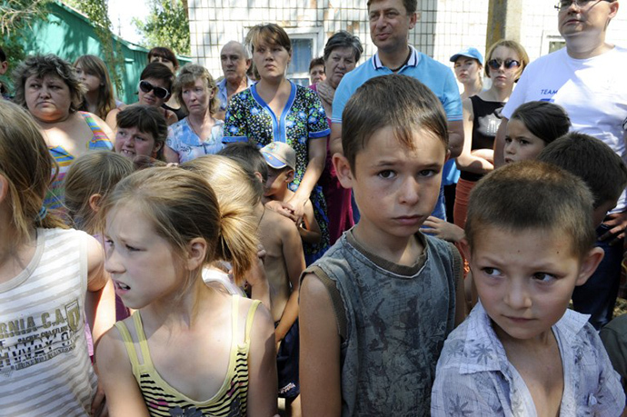 Women with their children, refugees from Donetsk and Lugansk regions, queue to receive humanitarian aid from the UN mission in Yalta, some 142 km from eastern Ukrainian city of Donetsk, on August 2, 2014. (AFP Photo / Alexander Khudoteply)