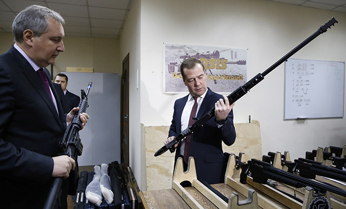 Russian Prime Minister Dmitry Medvedev (R) holds a weapon while listening to an explanation given by his deputy Dmitry Rogozin, during an inspection of Russian-made firearms at Promtechnologiya company in Moscow November 19, 2013. (Reuters / Dmitry Astakhov)