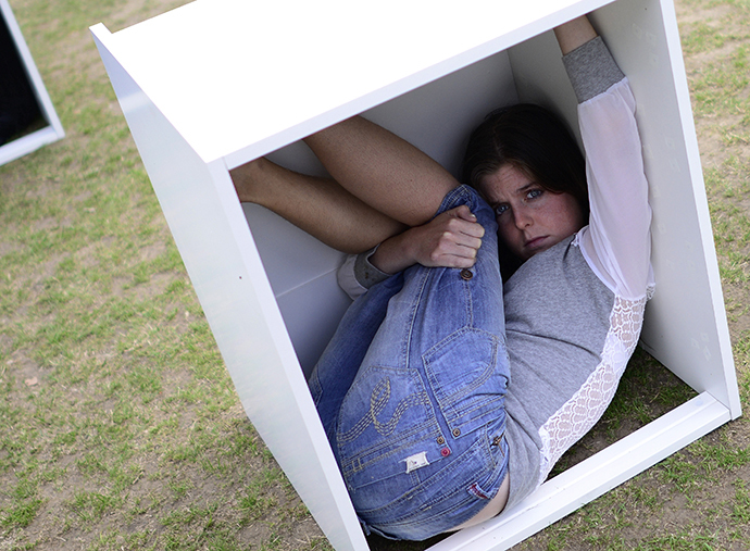 A volunteer sits in a wooden box at Parliament Square, to represent living conditions in Gaza, during a protest in London August 14, 2014. (Reuters / Dylan Martinez)