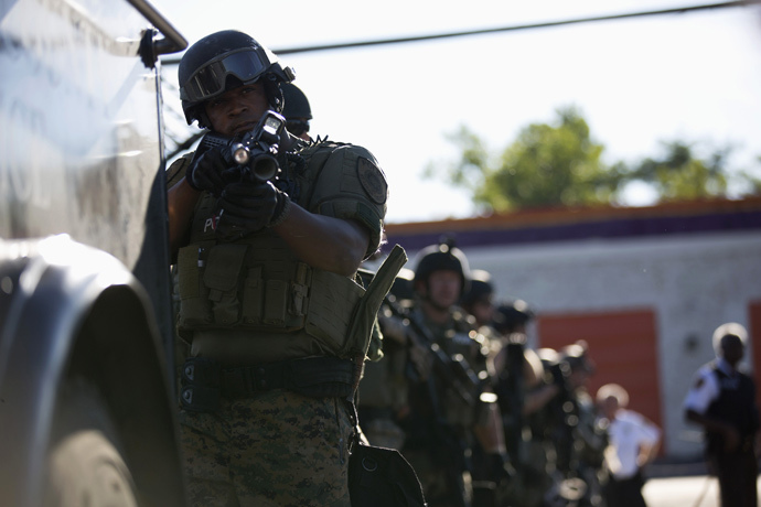 A police officer holds his riot gun while demonstrators protest the shooting death of teenager Michael Brown in Ferguson, Missouri August 13, 2014. (Reuters / Mario Anzuoni)