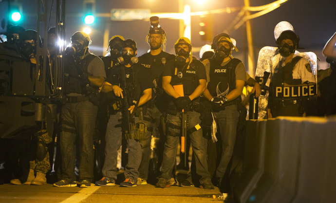 Police officers keep watch while demonstrators (not pictured) protest the death of black teenager Michael Brown in Ferguson, Missouri August 12, 2014. (Reuters / Mario Anzuoni)