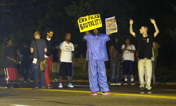 Demonstrators stand in the street in Ferguson, Missouri August 11, 2014. (Reuters / Mario Anzuoni)