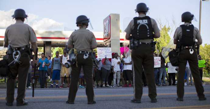Police officers watch as demonstrators protest the death of black teenager Michael Brown in Ferguson, Missouri August 12, 2014. (Reuters / Mario Anzuoni)