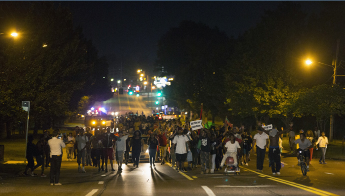 Demonstrators march in the street while protesting the shooting death of black teenager Michael Brown in Ferguson, Missouri August 12, 2014. (Reuters / Mario Anzuoni)
