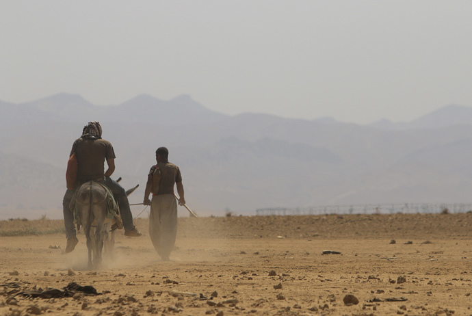 A displaced man from the Yazidi religious minority, fleeing violence from forces loyal to the Islamic State in Sinjar town, rides a donkey as he makes his way with another man towards the Mount Sinjar, after securing the evacuation process of their families towards the Syrian border August 13, 2014. (Reuters / Rodi Said)
