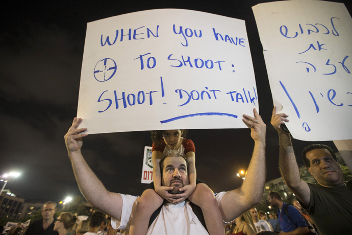 A man holds a sign during a rally in Tel Aviv's Rabin Square, to show solidarity with residents of Israel's southern communities, who have been targeted by Palestinian rockets and mortar salvoes, August 14, 2014. (Reuters / Baz Ratner)