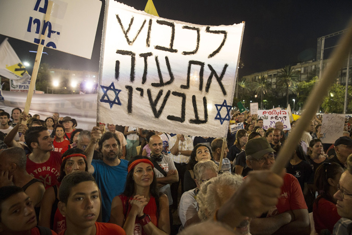 "People hold signs during a rally in Tel Aviv's Rabin Square, to show solidarity with residents of Israel's southern communities, who have been targeted by Palestinian rockets and mortar salvoes, August 14, 2014. The sign reads ""Conquer Gaza now"". (Reuters / Baz Ratner)"
