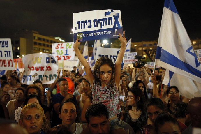 "Israelis gather during a protest calling on the government and the army to end Palestinian rocket attacks from Gaza once and for all, in the Mediterranean city of Tel Aviv on August 14, 2014. Hebrew writting on placard reads ""strong together."" (AFP Photo / Gali Tibbon)"