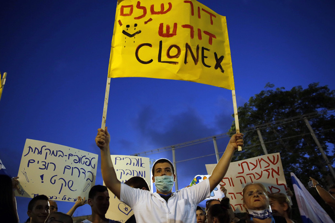 "Israelis gather during a protest calling on the government and the army to end Palestinian rocket attacks from Gaza once and for all, in the Mediterranean city of Tel Aviv on August 14, 2014. Hebrew writting on placard reads ""an entire generation demands clonex (anti-anxiety medication)."" (AFP Photo / Gali Tibbon)"