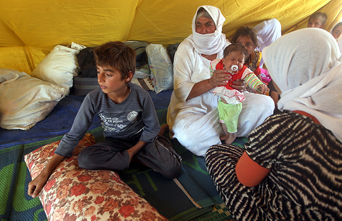 An Iraqi Yazidi refugee family sits inside a tent at Newroz camp in Hasaka province, north eastern Syria on August 14, 2014, after fleeing Islamic State militants in Iraq. (AFP Photo / Ahmad Al-Rubaye)