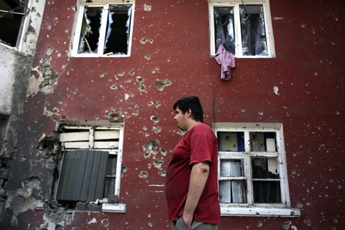A young resident walks past damaged buildings on August 14, 2014 in the small eastern Ukrainian city of Vuglegirsk, freed by the Ukraine's forces three days ago, in the Donetsk region. (AFP Photo / Anatolii Stepanov)