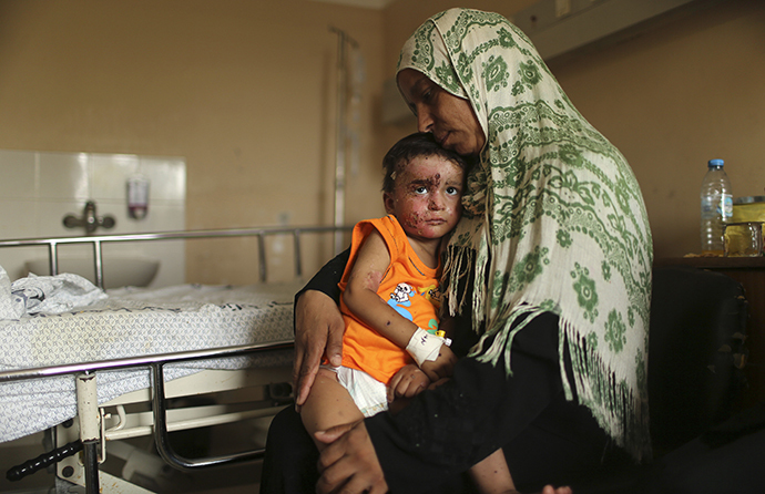 Palestinian boy Mohammed Wahdan, whom medics said was wounded in Israeli shelling, is held by his aunt as he receives psychological care at Shifa hospital in Gaza City August 14, 2014. (Reuters / Mohammed Salem)