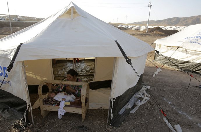 A woman from the minority Yazidi sect, who fled the violence in the Iraqi town of Sinjar, looks after her baby at Bajed Kadal refugee camp south west of Dohuk province August 15, 2014. (Reuters / Youssef Boudlal)