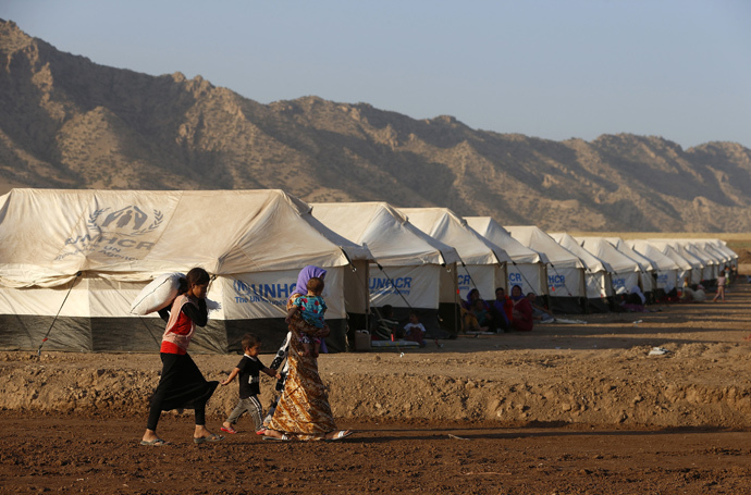 Displaced people from the minority Yazidi sect, who fled the violence in the Iraqi town of Sinjar, walk in Bajed Kadal refugee camp south west of Dohuk province August 15, 2014 (Reuters / Youssef Boudlal)
