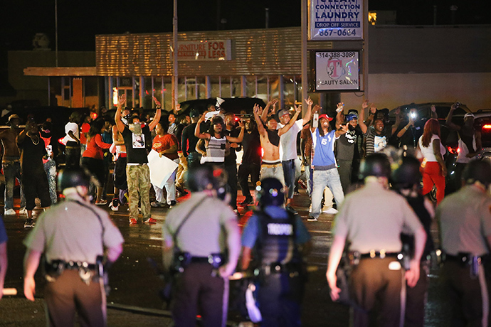 Demonstrators taunt police during a protest over the shooting death of Michael Williams on August 15, 2014 in Ferguson, Missouri, Police shot pepper spray, smoke, gas and flash grenades at protestors before retreating (AFP Photo / Scott Olson)