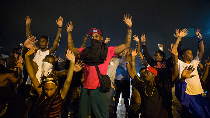 Demonstrators confront police with their arms raised during on-going demonstrations to protest against the shooting of Michael Brown, in Ferguson, Missouri, August 16, 2014 (Reuters / Lucas Jackson)