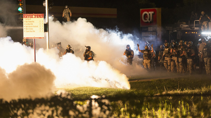 Riot police clear a street with smoke bombs while clashing with demonstrators in Ferguson, Missouri August 13, 2014. (Reuters / Mario Anzuoni)