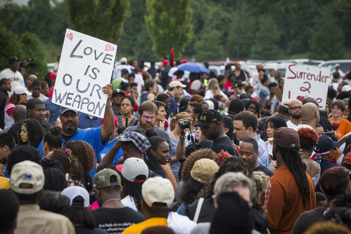 Demonstrators stand in an overflow crowd outside of a church where civil rights leader Al Sharpton spoke with community leaders, as communities continue to react to the shooting of Michael Brown, in Ferguson, Missouri August 17, 2014. (Reuters/Lucas Jackson)
