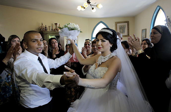 Groom Mahmoud Mansour, 26, and his bride Maral Malka, 23, celebrate with friends and family before their wedding in Mahmoud's family house in Jaffa, south of Tel Aviv August 17, 2014. (Reuters / Ammar Awad)