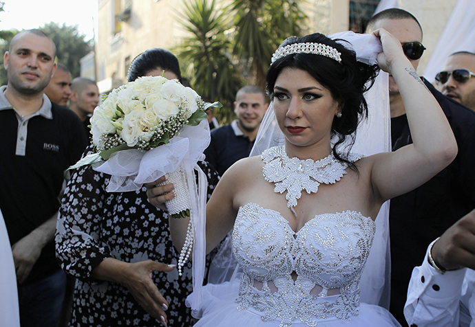 Bride Maral Malka, 23, celebrates with friends and family before her wedding to groom Mahmoud Mansour, 26, (not pictured) in Jaffa, south of Tel Aviv August 17, 2014. (Reuters / Ammar Awad)