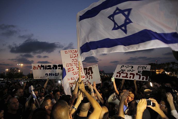 Protesters hold signs and shout slogans against the wedding of groom Mahmoud Mansour, 26, and bride Maral Malka, 23, outside a wedding hall in Rishon Lezion, near Tel Aviv August 17, 2014. (Reuters / Ammar Awad)