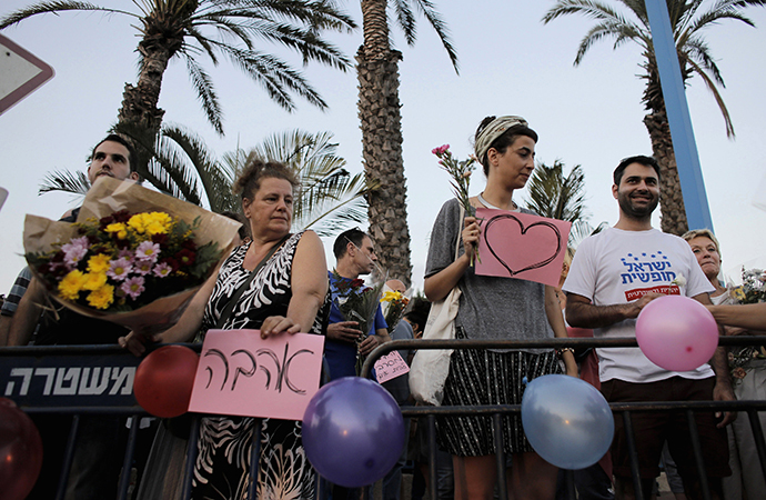 Protesters hold signs in support of the wedding of groom Mahmoud Mansour, 26, and bride Maral Malka, 23, outside a wedding hall in Rishon Lezion, near Tel Aviv August 17, 2014. (Reuters / Ammar Awad)