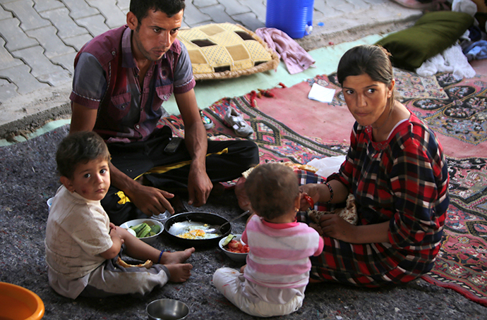 A displaced Iraqi family from the Yazidi community eat under a bridge where they found refuge after Islamic State (IS) militants attacked the town of Sinjar on August 17, 2014 on the outskirts of the Kurdish city of Dohuk, in Iraq's autonomous Kurdistan region. (AFP Photo / Ahmad Al-Rubaye)