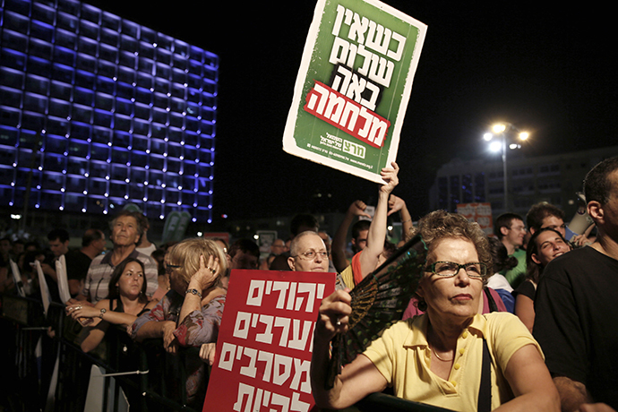 "A demonstrator holds up placards reading in Hebrew: ""When there is no peace war comes"" (top) and ""Jews and Arabs refuse to be enemies"" (bottom) as thousands of Israelis protest during a left-wing peace rally in the coastal city of Tel Aviv calling for the Israeli government to negotiate with the Palestinian Authority on August 16, 2014. (AFP Photo / Gali Tibbon)"