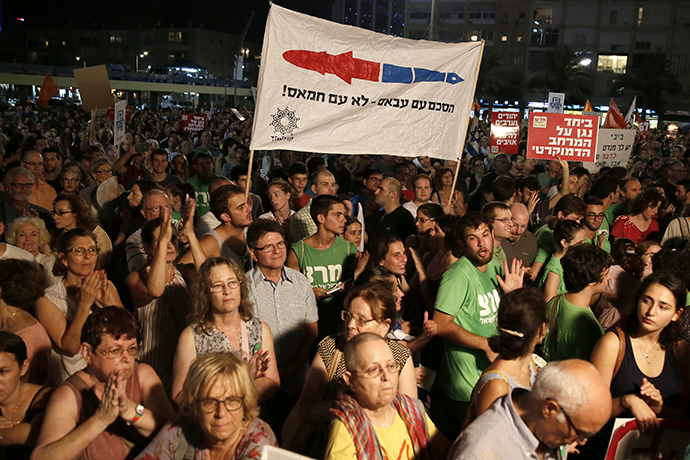 "Demonstrators hold a placard reading in Hebrew: ""Agreement with Abbas not with Hamas"" as thousands of Israelis protest during a left-wing peace rally in the coastal city of Tel Aviv calling for the Israeli government to negotiate with the Palestinian Authority on August 16, 2014. (AFP Photo / Gali Tibbon)"
