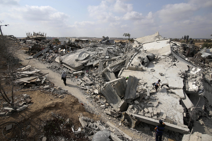 A Palestinian woman walks past the ruins of houses which witnesses said were destroyed during the Israeli offensive in Johr El-Deek village near the central Gaza Strip August 17, 2014. (Reuters / Ibraheem Abu Mustafa)