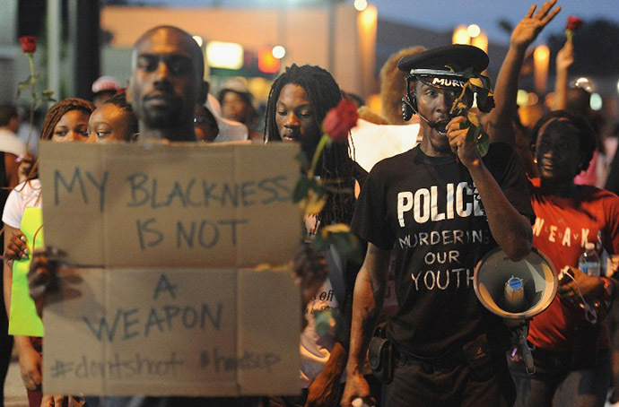 A demonstrator displays a sign during a protest in Ferguson, Missouri on August 18, 2014. (AFP Photo / Getty Images / Michael B. Thomas)