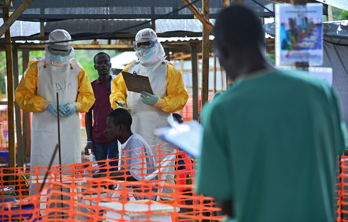An MSF medical worker, wearing protective clothing relays patient details and updates behind a barrier to a colleague at an MSF facility in Kailahun, on August 15, 2014. (AFP Photo / Carl de Souza)