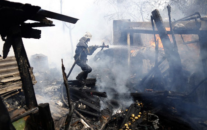 A firefighter extinguishes a fire in a suburb of Donetsk after a shelling on August 17, 2014. (AFP Photo / Max Vetrov)