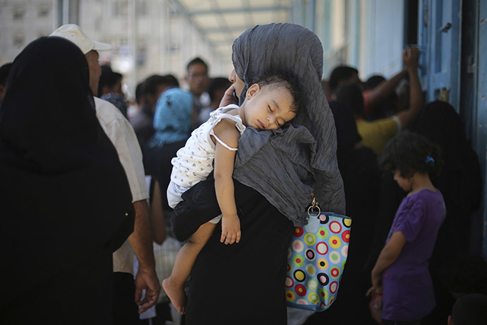 A Palestinian woman holds her daughter as she waits to receive food supplies from a United Nations food distribution center in Khan Younis in the southern Gaza Strip August 19, 2014. (Reuters / Ibraheem Abu Mustafa)