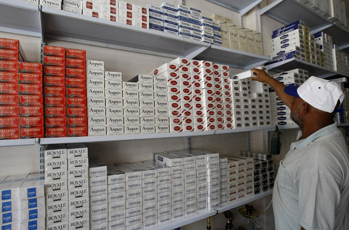 An Iraqi man takes a carton of cigarettes from a shop in Baghdad (AFP Photo / Sabah Arar)