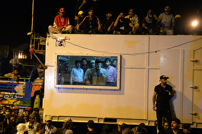 "Canada-based preacher Tahir-ul-Qadri (2nd R-in window) addresses supporters from inside a shipping container in front of the parliament building during the ""Revolution March"" protest in Islamabad on August 20, 2014. (AFP Photo / Aamir Qureshi)"