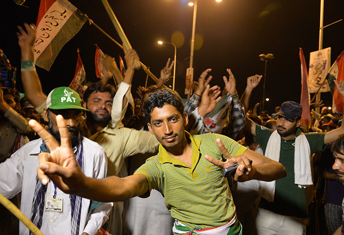 "Pakistani supporters of Canada-based preacher Tahir-ul-Qadri dance as they gather in front of the parliament building during the ""Revolution March"" protest in Islamabad on August 20, 2014. (AFP Photo / Aamir Qureshi)"