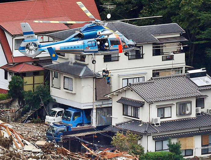 A local resident is lifted by a rescue helicopter from an area where a landslide swept through a residential area at Asaminami ward in Hiroshima, western Japan, in this photo taken by Kyodo August 20, 2014. (Reuters / Kyodo)