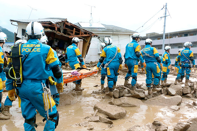 Rescue units of police officers walk during a rescue operation after a massive landslide swept through a residential area at Asaminami ward in Hiroshima, western Japan, in this photo taken by Kyodo August 20, 2014. (Reuters / Kyodo)