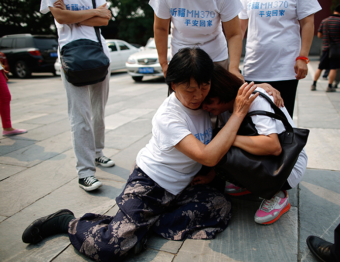 A family member of a passenger aboard the missing Malaysia Airlines flight MH370 comforts another relative as they gather to pray at Yonghegong Lama Temple in Beijing (Reuters / Kim Kyung-Hoon)
