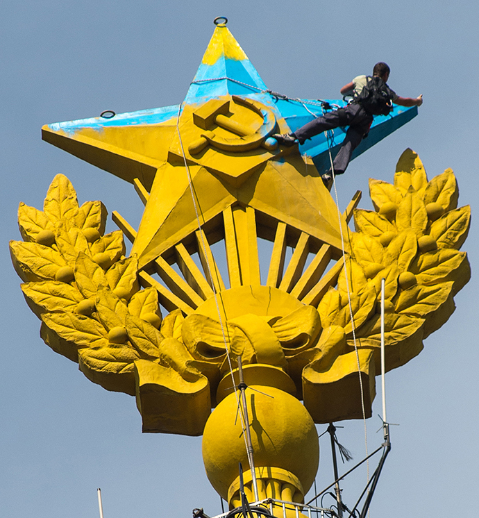 A worker paints the star on the spire of the Stalinist building at Kotelnicheskaya Embankment in Moscow that was painted blue by unidentified people (RIA Novosti / Ramil Sitdikov)