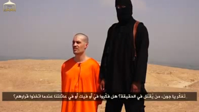 An American Journalist, James Foley, is seen kneeling adjacent to a masked Islamic State (IS) militant prior to his alleged brutal beheading with a knife. (Screenshot from youtube.com/user/majed0001)