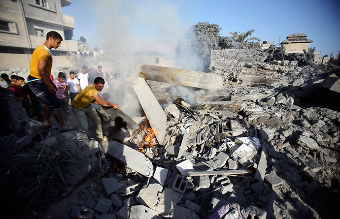 Palestinians try to put out a fire from the rubble of a house, which witnesses said was destroyed in an Israeli air strike, in Rafah in the southern Gaza Strip August 20, 2014 (Reuters / Ibraheem Abu Mustafa)