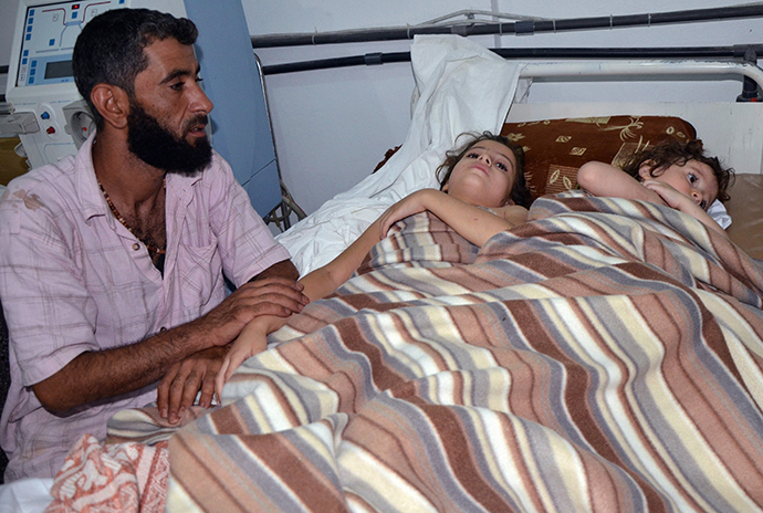 A man sits in a hospital near two children who activists say were affected by nerve gas in the Ghouta region, in the Duma neighbourhood of Damascus August 21, 2013 (Reuters / Bassam Khabieh)