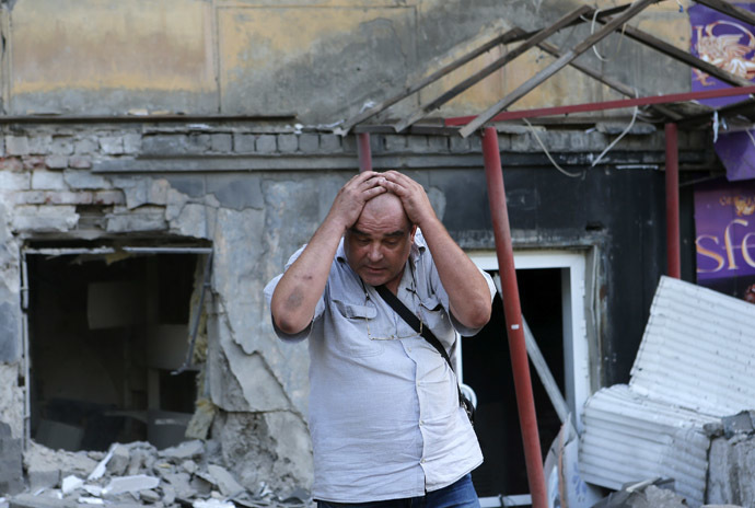 A man reacts as he stands in front of a building damaged by, what locals say, was recent shelling by Ukrainian forces, in Donetsk, August 20, 2014. (Reuters/Maxim Shemetov)