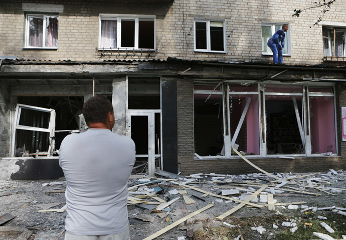A local resident stands in front of an apartment block damaged by a recent shelling in the settlement of Makeyevka, on the outskirts of Donetsk, August 19, 2014. (Reuters/Maxim Shemetov)