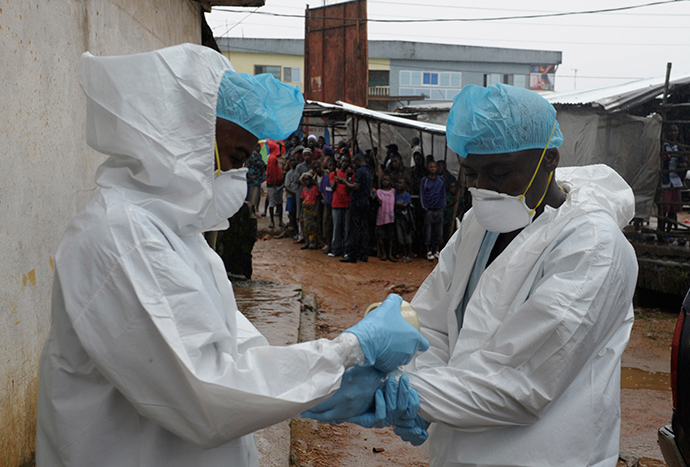 Health workers wear protective clothing before carrying an abandoned dead body presenting with Ebola symptoms at Duwala market in Monrovia August 17, 2014 (Reuters / 2Tango)