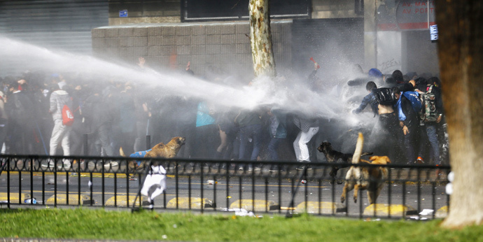 Demonstrators are hit by a jet of water during a demonstration against the government to demand changes in the education system in Santiago, August 21, 2014. (Reuters / Ivan Alvarado)