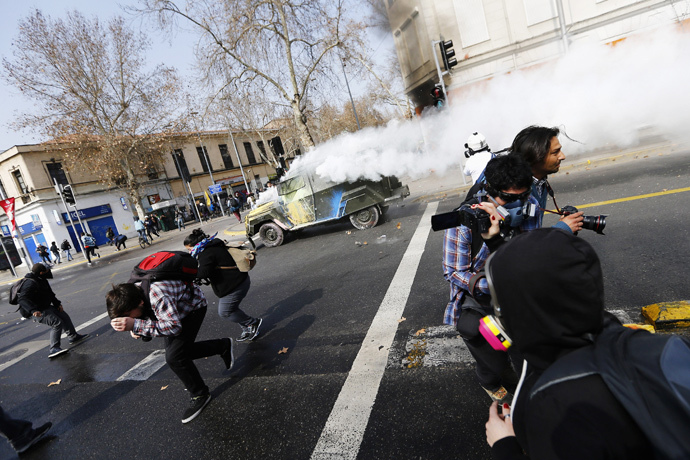 A riot police vehicle releases tear gas during a demonstration against the government to demand changes in the education system in Santiago, August 21, 2014. (Reuters / Ivan Alvarado)